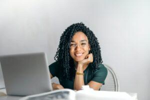 Glückliche Frau am Laptop in virtuellem Seminar
