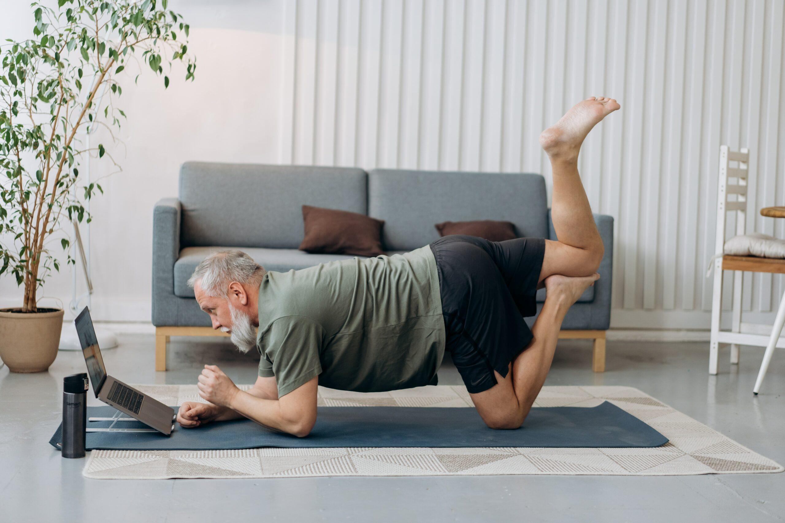 Mann macht Sport zu Hause vor dem Laptop